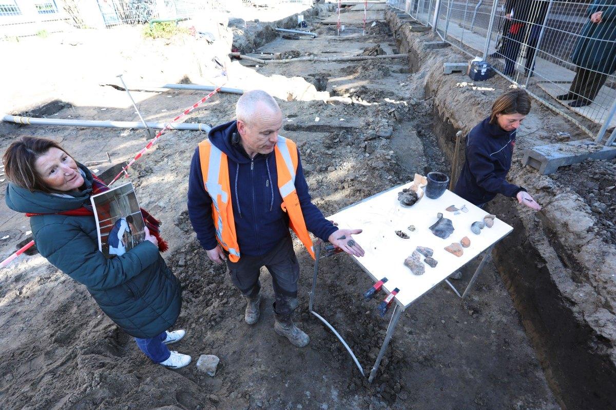 Annette Bakker, Nils Kerkhove en Marieke Arkema tonen vondsten in de Oudwijkerdwarsstraat. Foto: Ton van den Berg