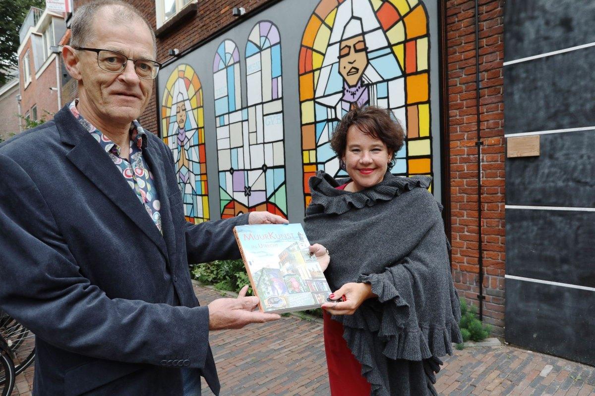 Joost van Waert overhandigt zijn Muurkunst aan burgemeester Sharon Dijksma. Foto: Ton van den Berg
