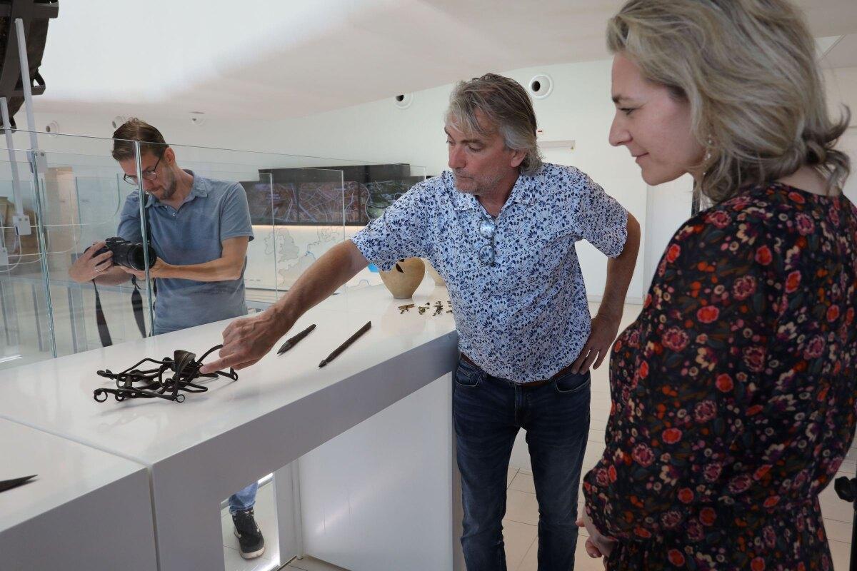 Wethouder Anke Klein ziet hoe archeoloog Erik Graafstal wijst op het Romeinse paardentuig. Onder zijn arm ligt de bijzondere battistapijl. Foto: Ton van den Berg