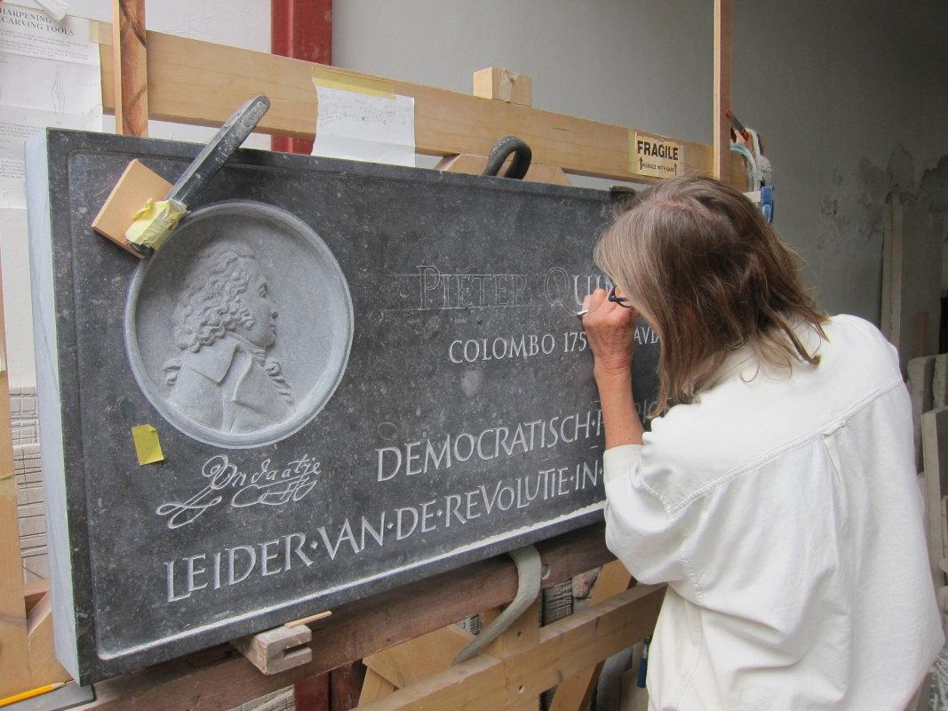 Britt Nelemans werkt aan de gevelsteen voor patriottenleider Pieter Quint Ondaatje. Foto: Paul Verhagen/UGTF.