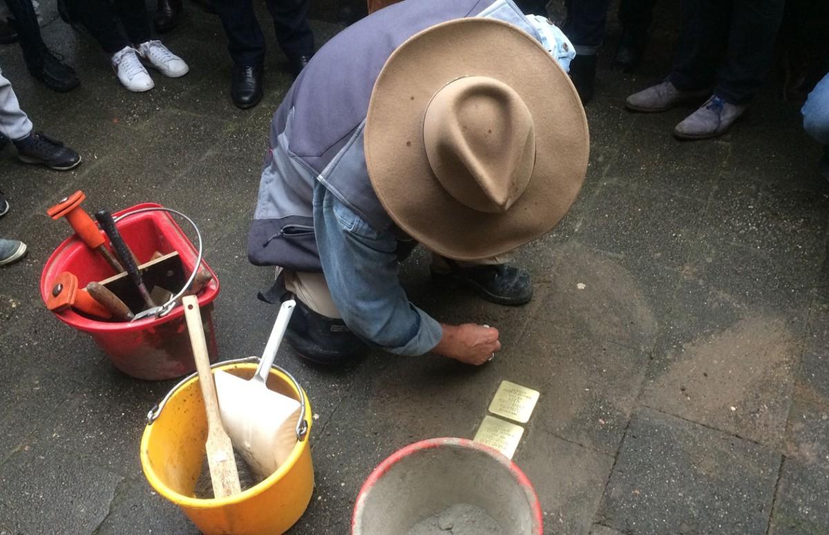 Een ontroerend gebaar: Gunter Demnig veegt op Mauritsstraat 93 na zijn werk de steentjes schoon. Foto: Jim Terlingen