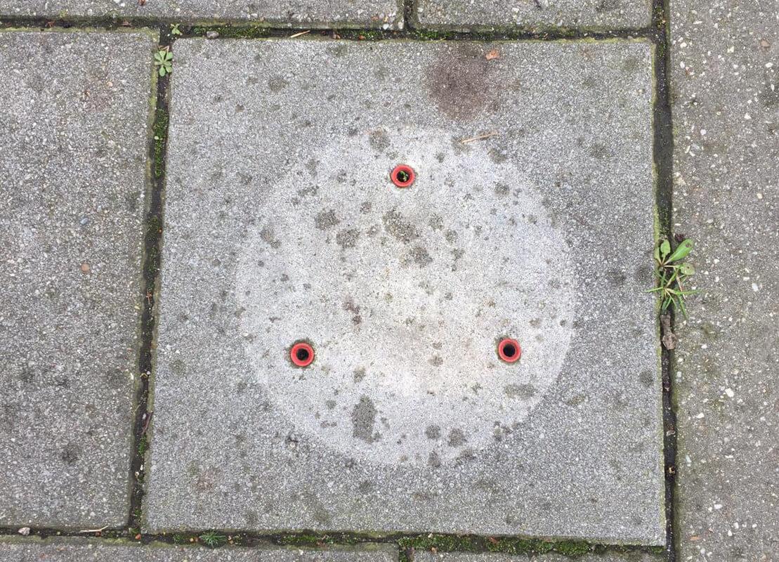 Drie gapende gaten op een stoepsteen en daaromheen een verkleuring met een ronde vorm.  Foto: J. Terlingen