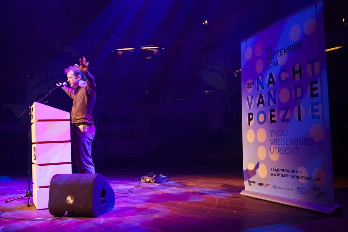 De dichter Alexis de Roode op het podium van de grote zaal. Foto: Ton van den Berg