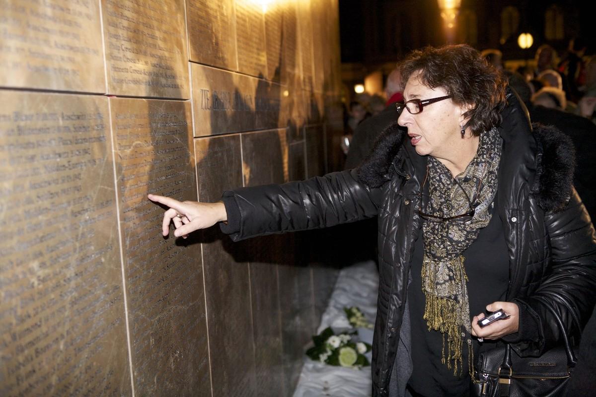 Een vrouw zoekt naar de namen op het Joods Monument. Foto: Ton van den Berg