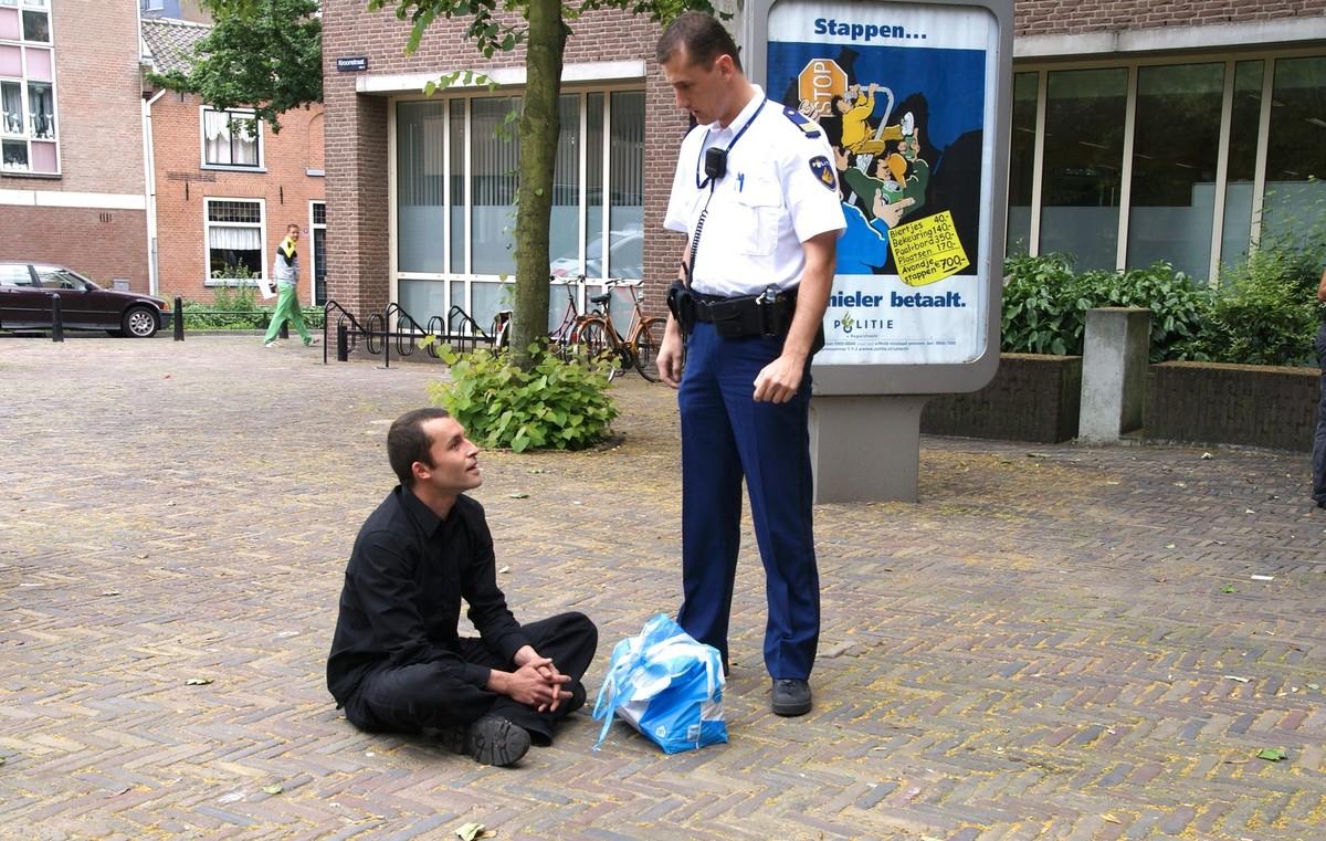 Kraker Rogier in 2008 in gesprek met een politieagent nadat hij drie waterverfbommetjes tegen de gevel van politiebureau Paardenveld heeft gegooid. Foto's Ton van den Berg