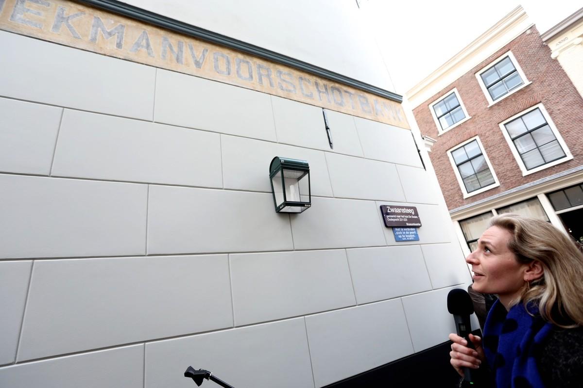 Wethouder Klein bij de onthulling van de ontdekte muurreclame. Foto: Ton van den Berg