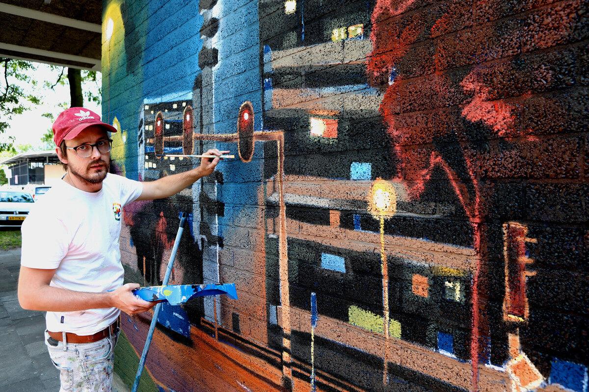 De Verfdokter aan het werk op een muur in het Tuindorp-West Complex. Foto: Ton van den Berg