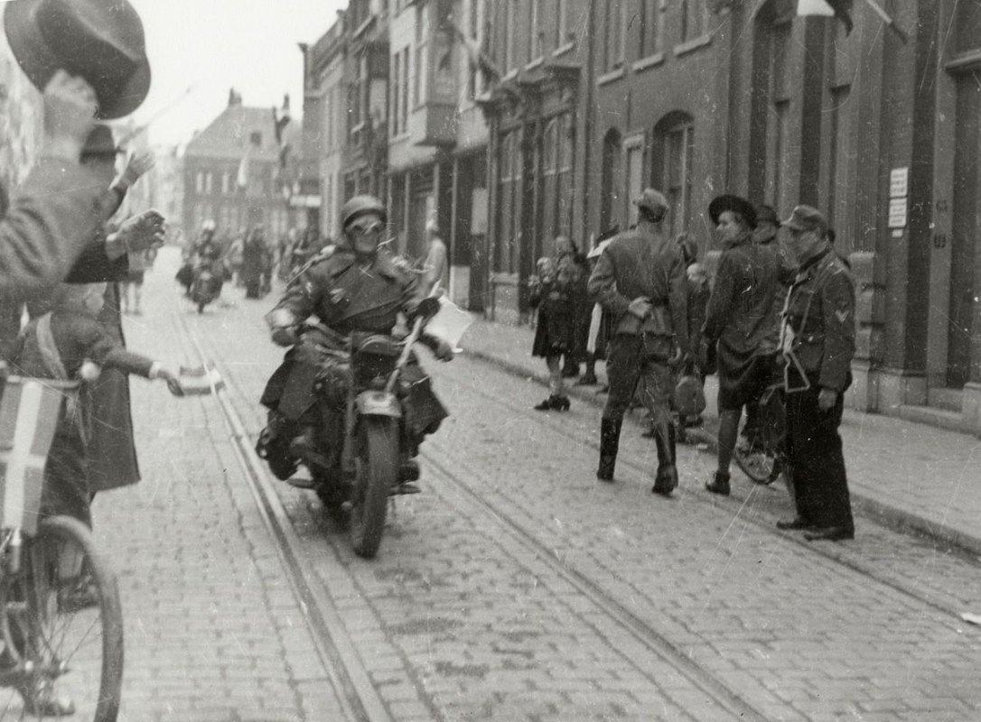 Drie Canadese motorrijders in de Voorstraat op weg naar het Academisch ziekenhuis worden toegejuicht, een Duitse soldaat met mitrailleur staart naar wat er voorbij komt. Foto: Collectie HUA