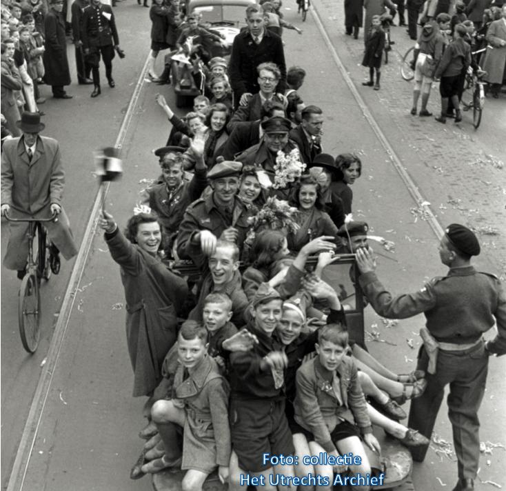 Vooral jongeren kruipen op de voertuigen van de Canadezen. Foto:  A.M. Stirton (National Archives of Canada)
