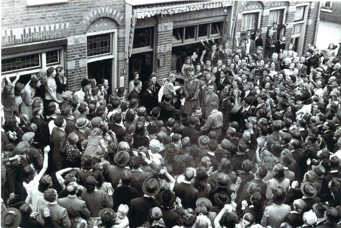 Twee kaalgeknipte vrouwen in een grote menigte in de Van der Helsstraat. Foto: Hogeweg