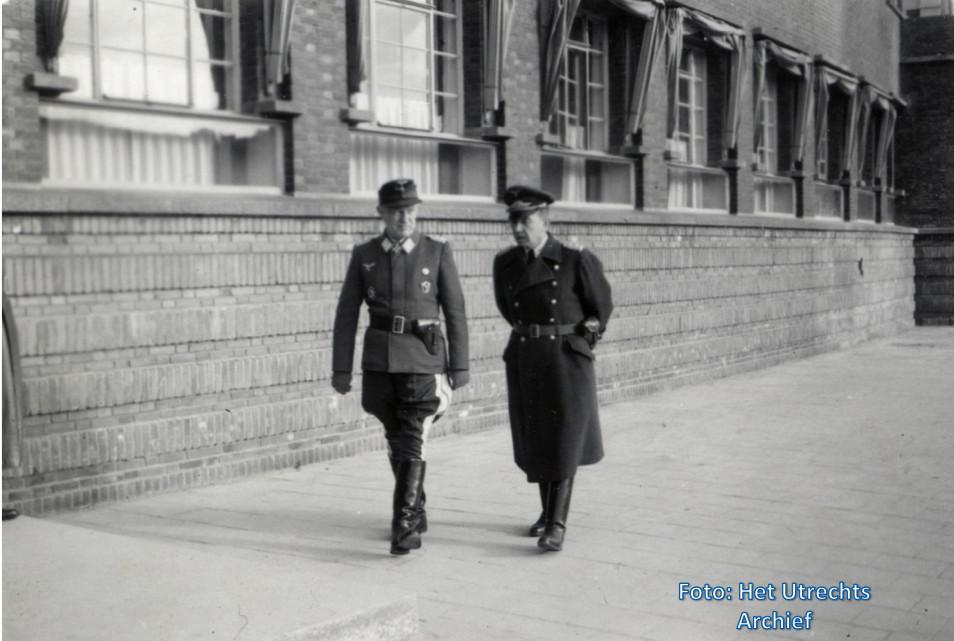 Een Duitse officier van de Wehrmacht en een Utrechtse politieman voor het Hoofdbureau van Politie op het Paardenveld, 1941-1943. Foto: HUA
