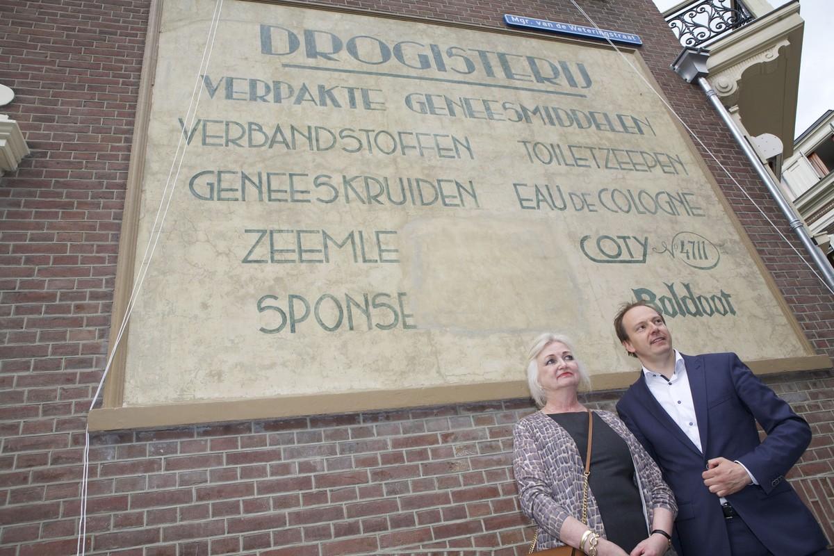 Wethouder Kreijkamp en bewoner Sylvia Six bij de herstelde muurreclame. Foto: Ton van den Berg