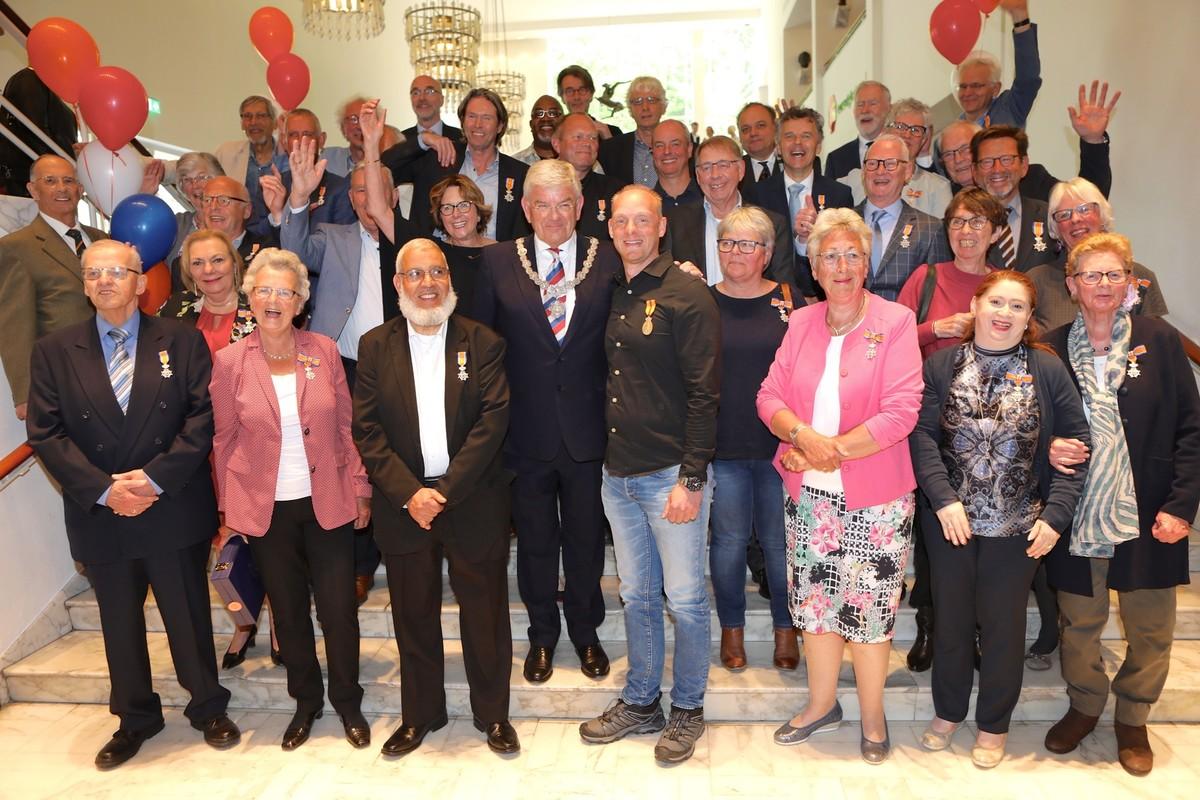 De 36 gedecoreerden met burgemeester Van Zanen op de trappen in de Stadsschouwburg. Foto's: Ton van den Berg